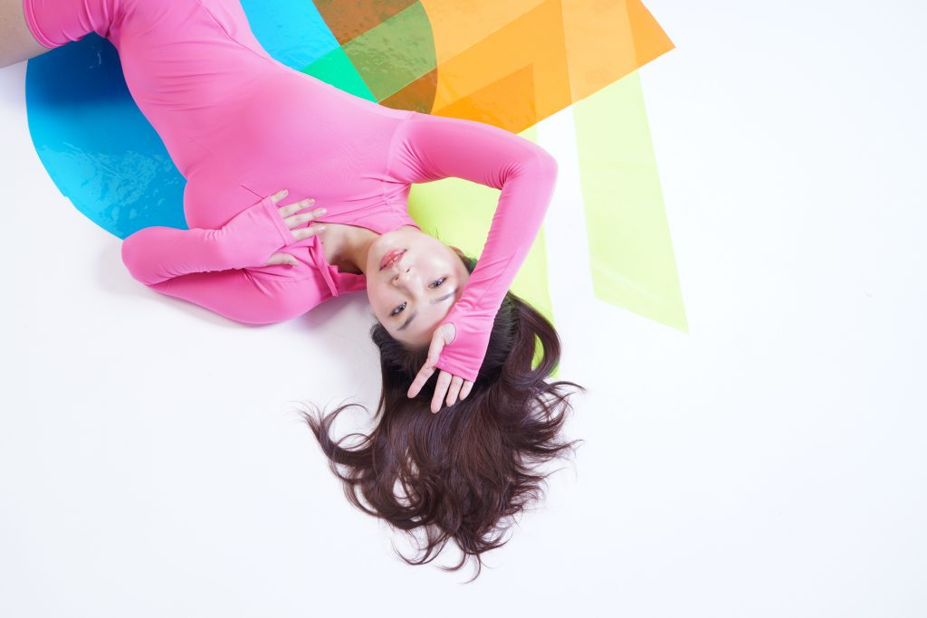 An overview photo of Shanghi Shawty. She is posing lying down on her back with colourful vinly cutouts surrounding her.